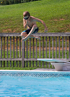 child jumping in swimming pool