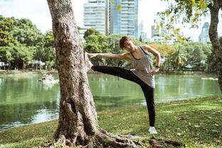 athletic woman stretching leg on tree by city pond